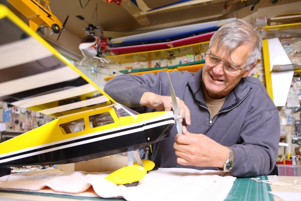 older gentleman fixing the propeller on a yellow and black model airplane in his workshop