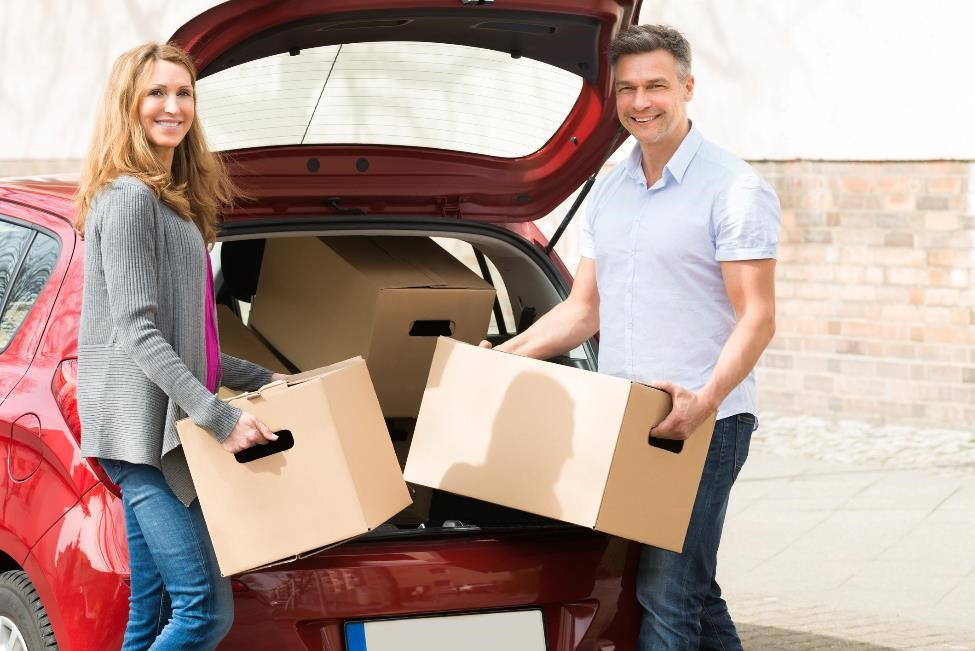 middle-aged couple loading moving boxes into red car