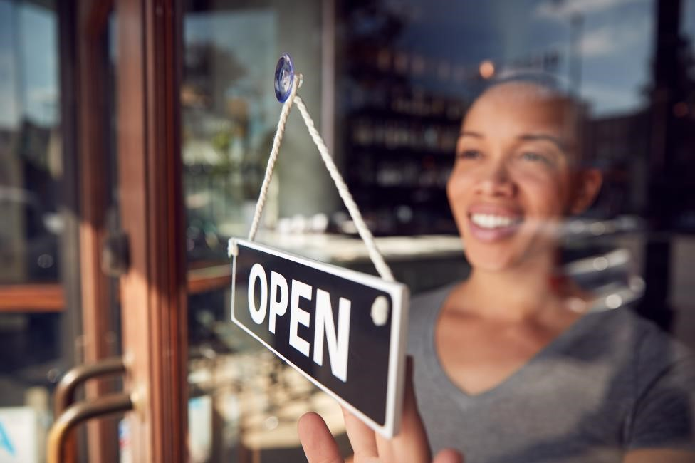 woman turning a business's window sign from open to closed