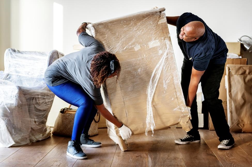 two people wrapping furniture in plastic to prep for moving
