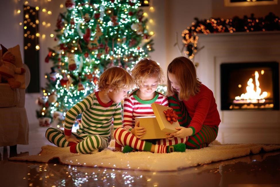 three children sitting in front of a Christmas tree opening gifts