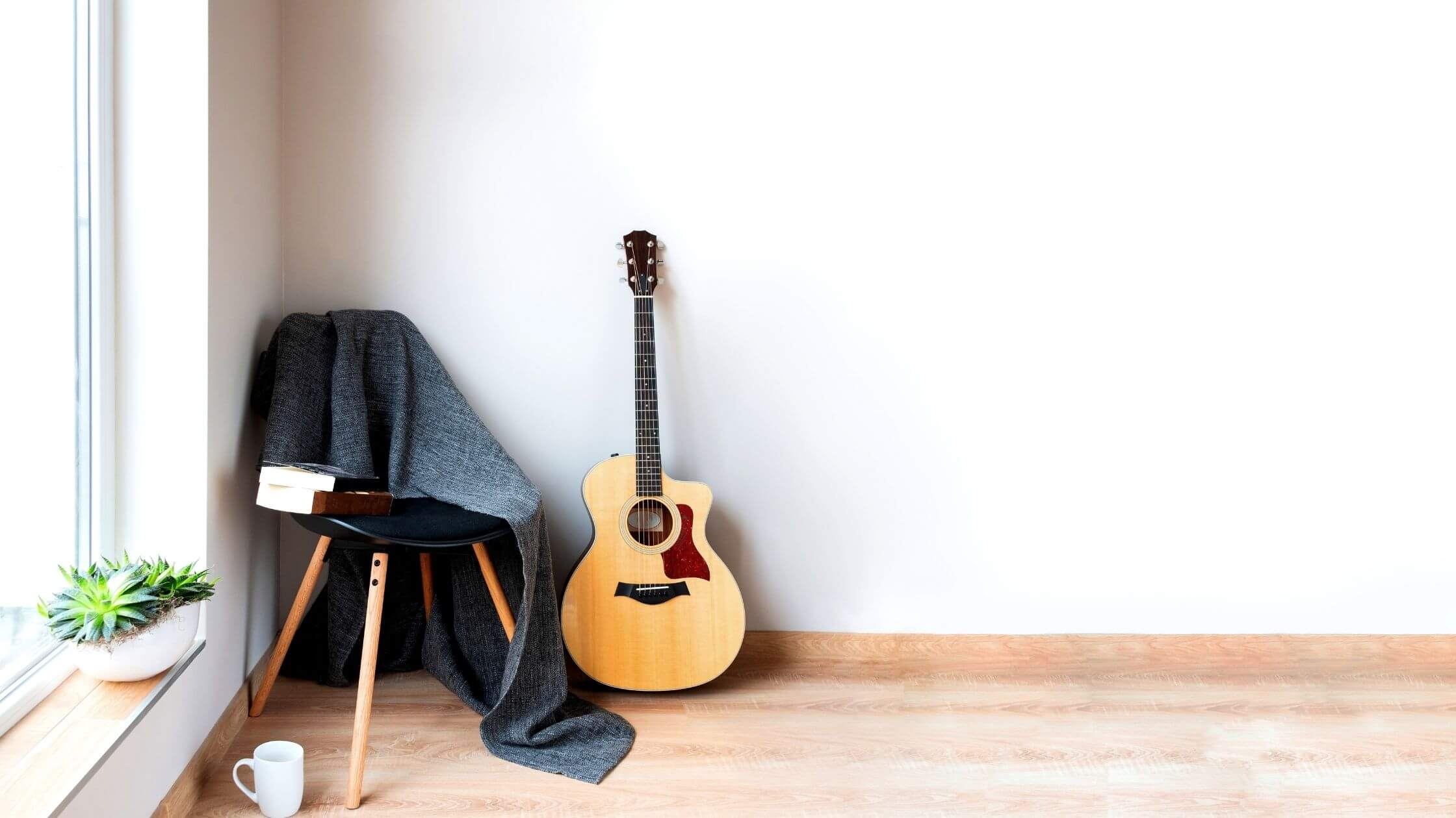 guitar leaning against a chair in a white room