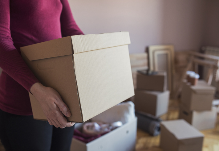 A woman organizing boxes of household items for self storage.